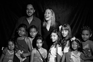 """Piper Perabo (top center) with Manolo Cardona (top left) pose for a photograph with local girls before an screening of """"Covert Affairs."""