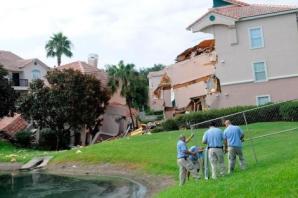 Varios trabajadores del Summer Bay Resort colocan vallas cerca del socavón.