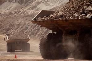 Mining trucks travel along a road at Chile's Esperanza copper mine near Calama town